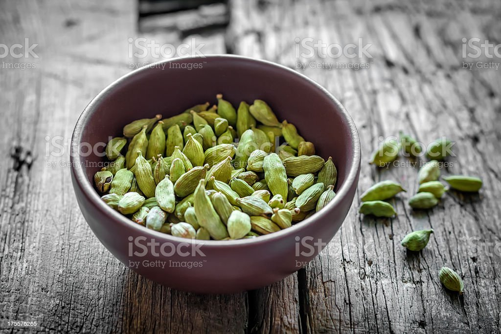 A brown small bowl of cardamom beans stock photo