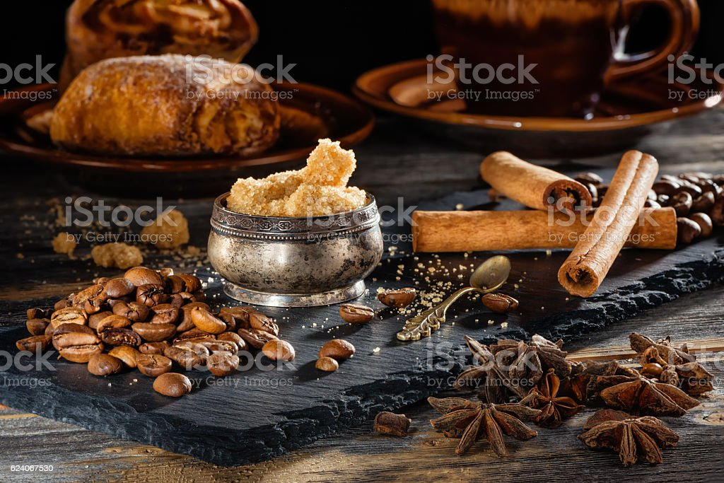Brown sugar, coffee grains and sticks of cinnamon on a stock photo