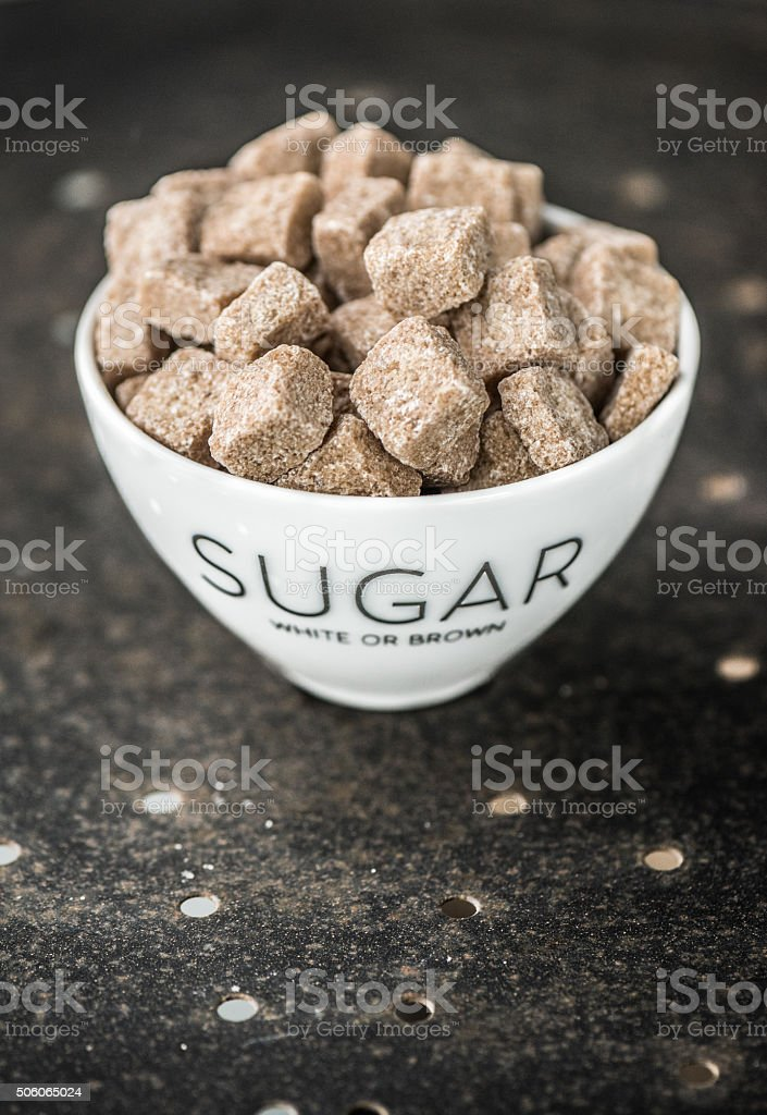 Brown sugar cubes in a cup stock photo