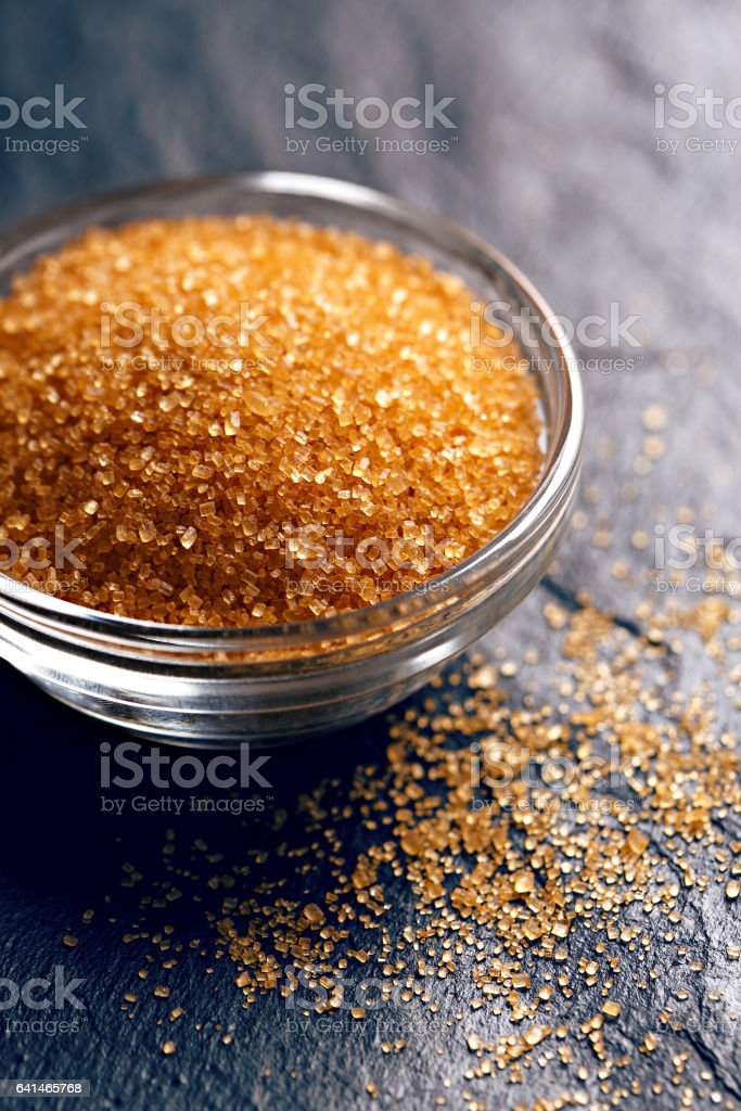 Brown sugar in a bowl on a black stone background. Top perspective view stock photo