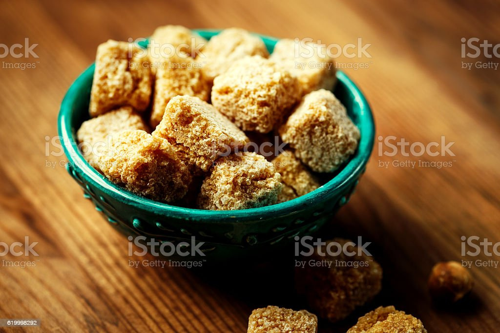 Brown sugar in a bowl on wooden background stock photo
