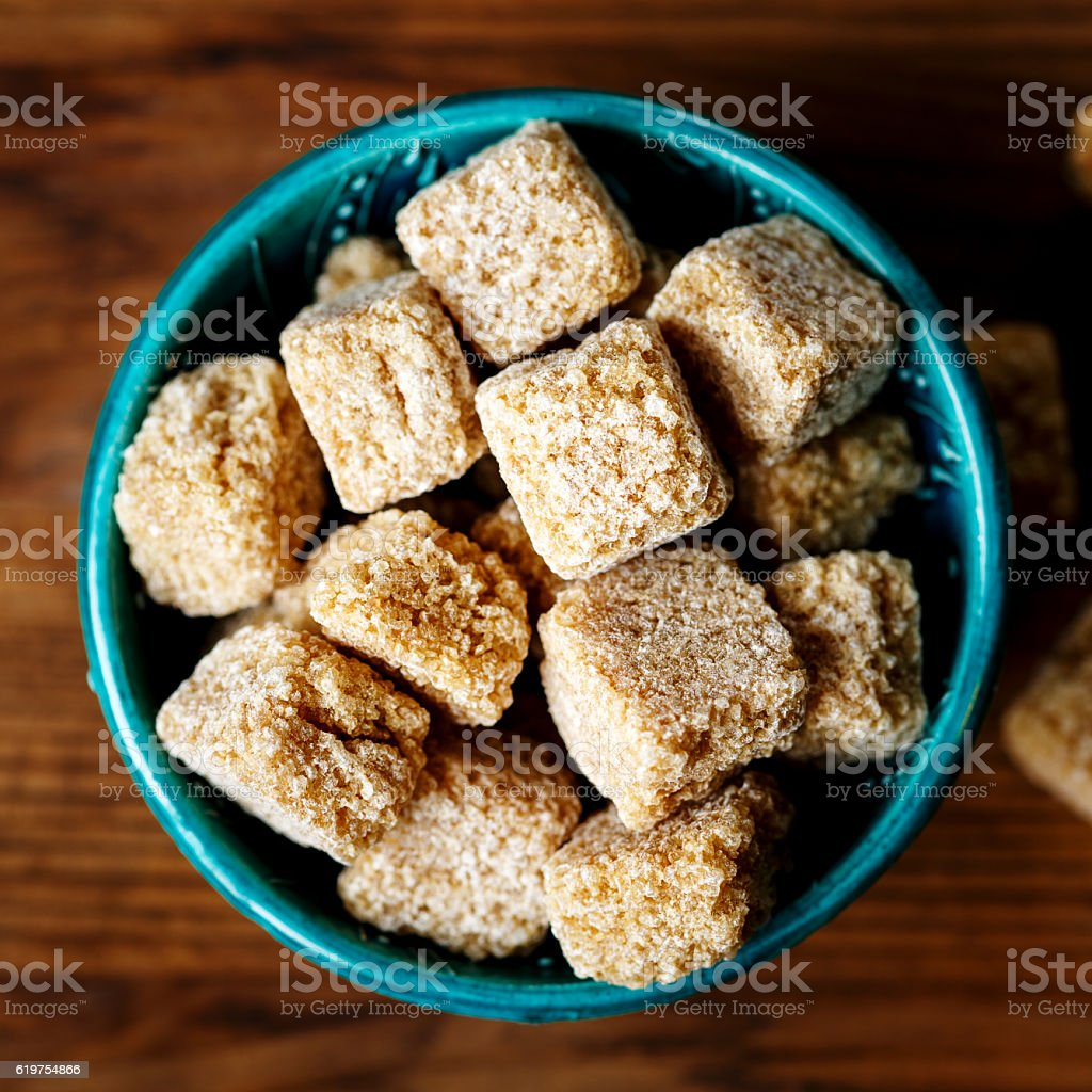 Brown sugar pieces in a bowl stock photo