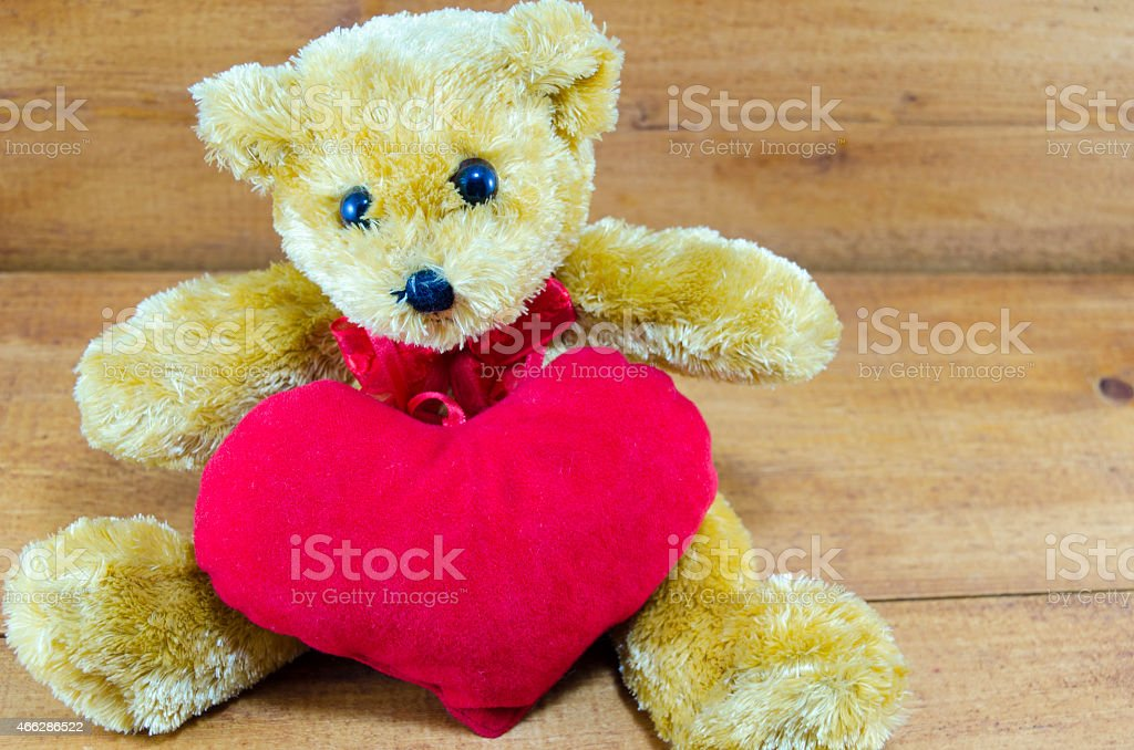 Brown teddy bear hugging a big red heart royalty-free stock photo
