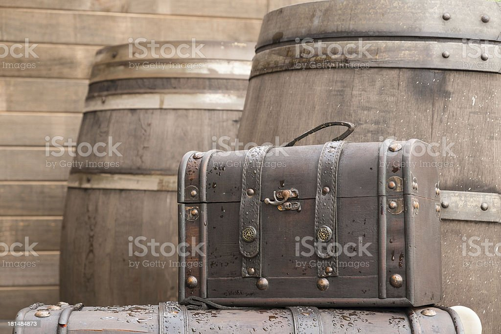 Brown vintage bag with wooden barrel background royalty-free stock photo