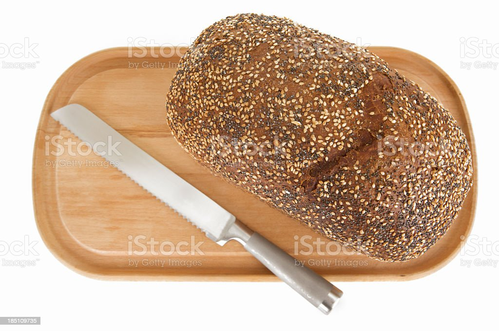 Brown wholemeal loaf with bread knife on wooden board stock photo