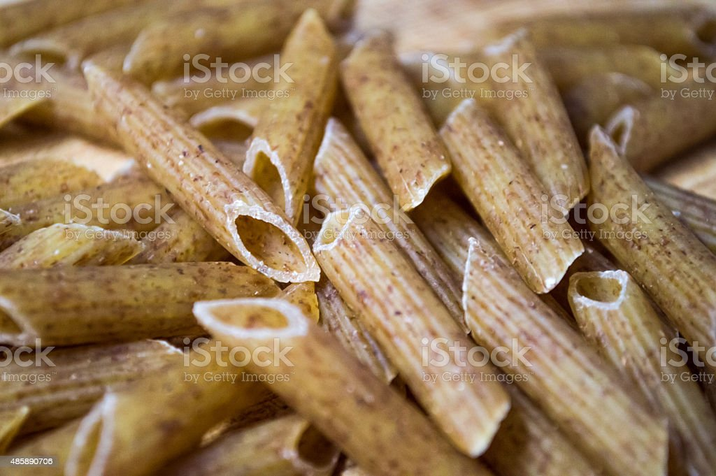 Brown Wholewheat/Meal/Grain Dry Penne Pasta Background royalty-free stock photo