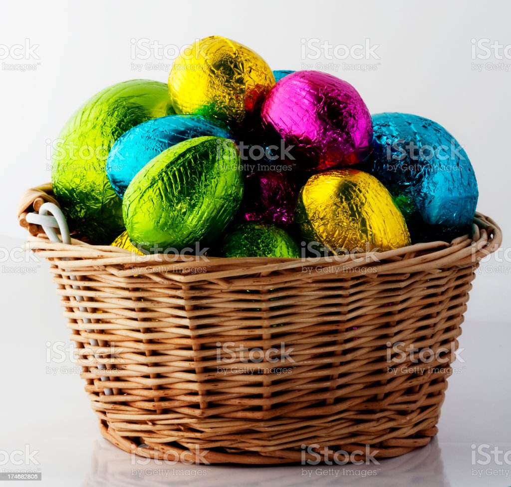 A brown wicker basket filled with shiny multicolor eggs  royalty-free stock photo