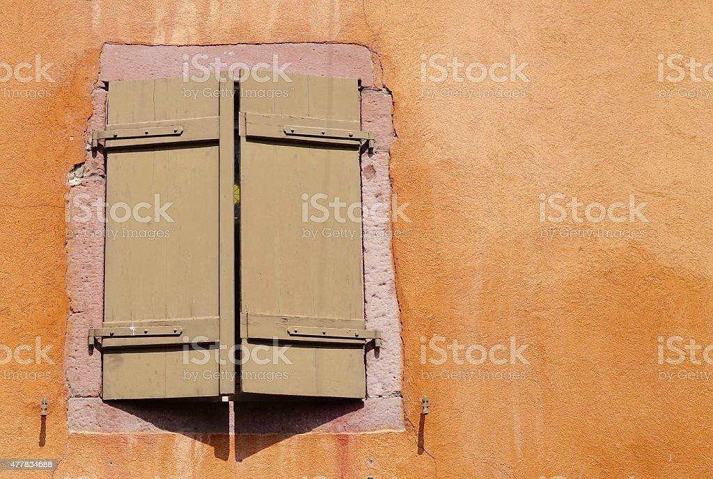 brown window shutter of an orange house stock photo
