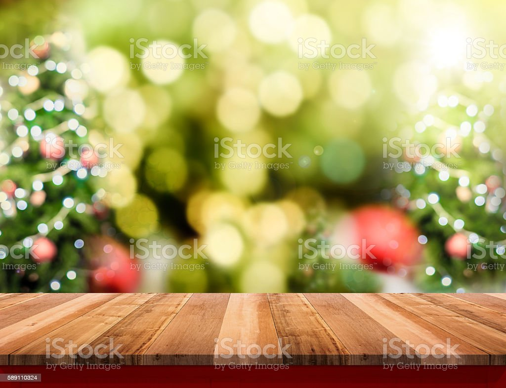 Brown Wood table top with abstract blur christmas tree stock photo