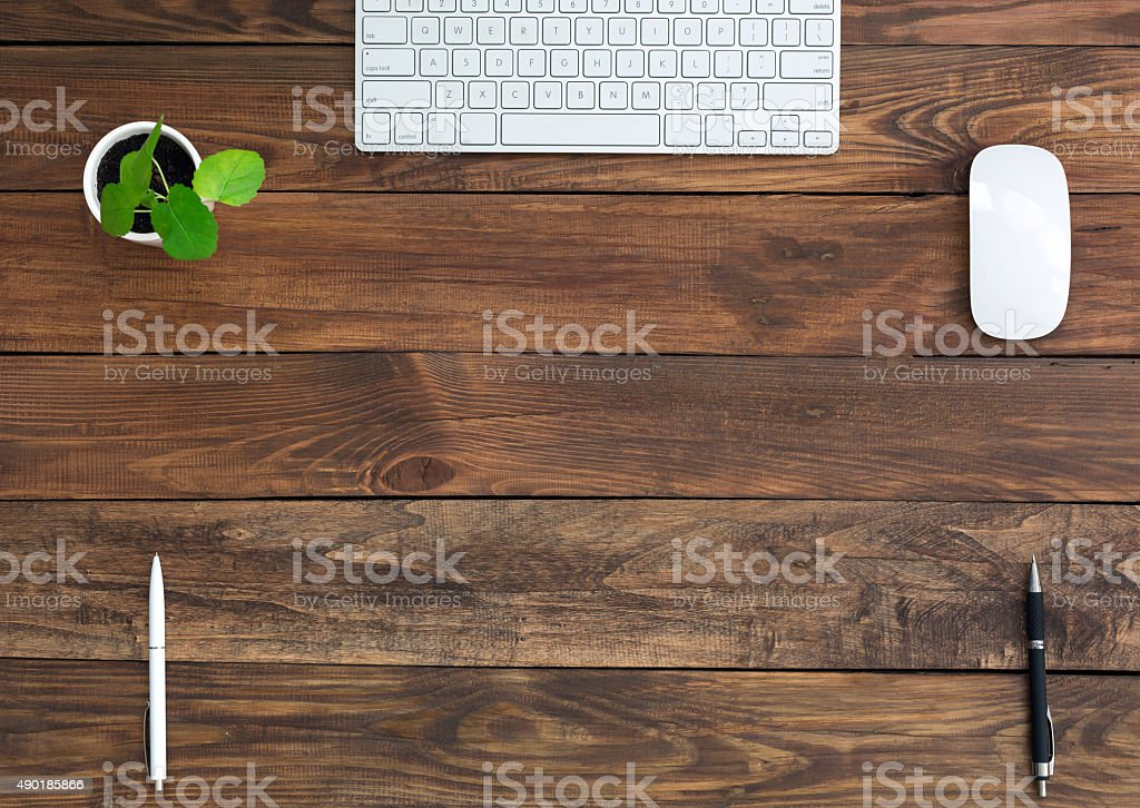 Brown Wooden Desk with Stationery and Electronics stock photo