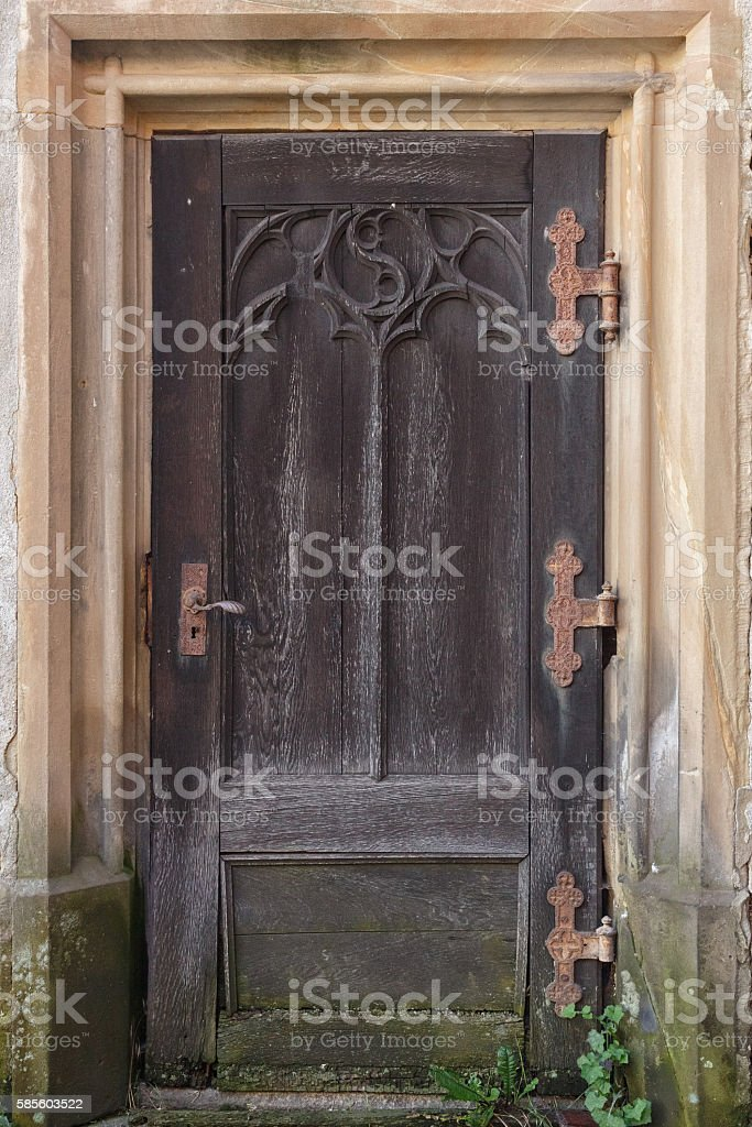 Brown wooden door of an obsolete medieval church in Bavaria stock photo