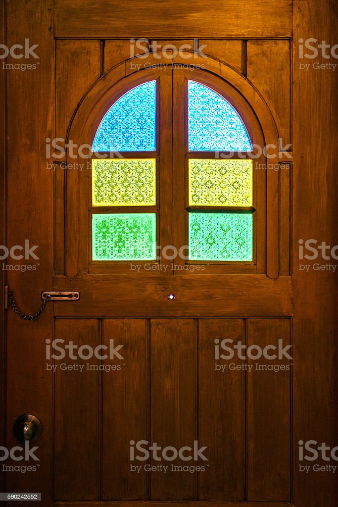 Brown wooden door with colorful stained glass photo libre de droits