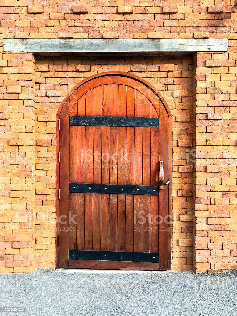 Brown wooden door with red brick wall stock photo