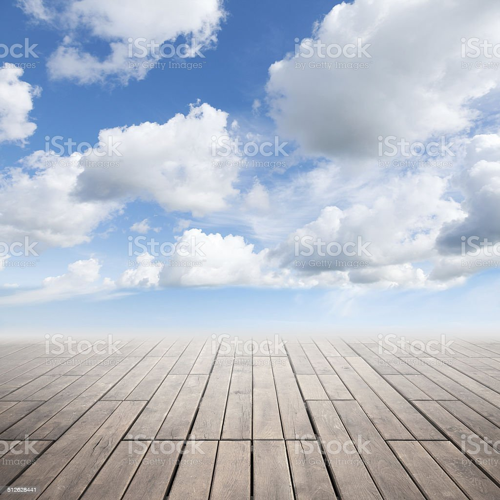 Brown wooden floor with perspective and cloudy sky stock photo