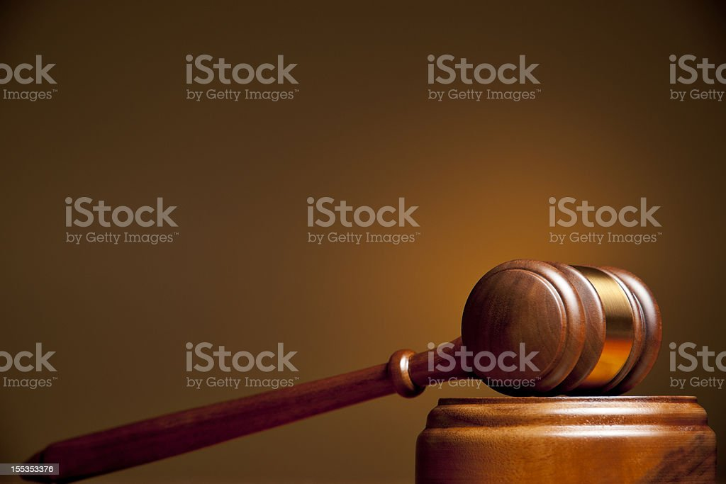 Brown wooden gavel laying on its side on sound block stock photo