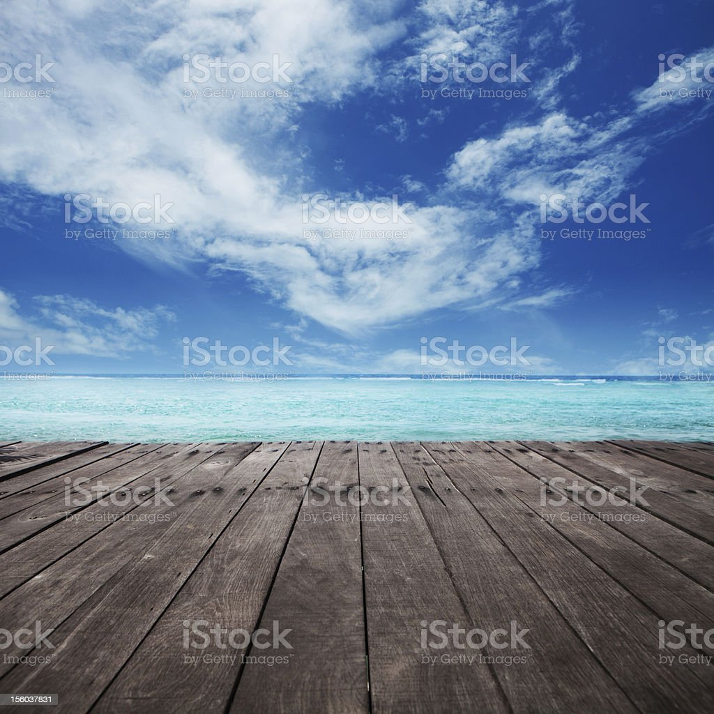 Brown wooden platform under cloudy blue sky stock photo