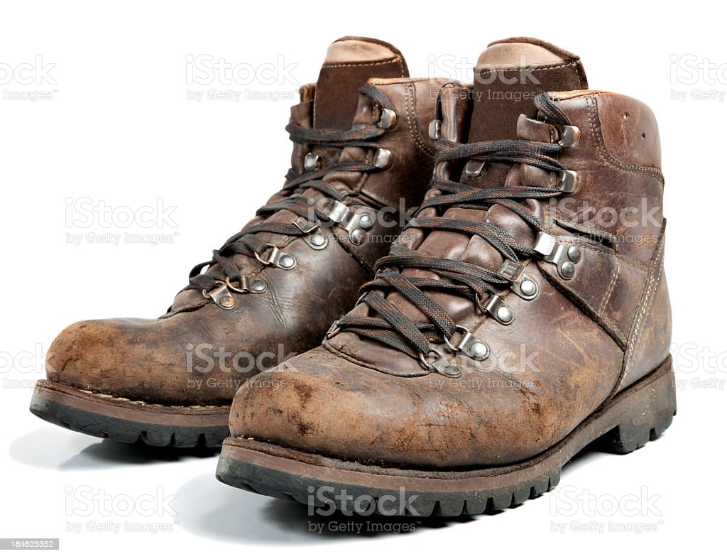 Brown worn hiking boots on white background stock photo
