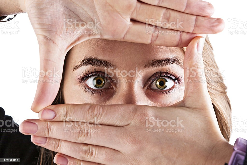 Brown-eyed blonde frames face with fingers and looks through stock photo