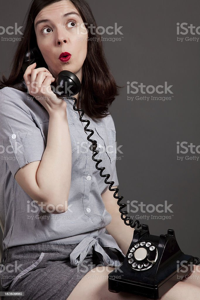 Brown-haired woman with a vintage black dial telephone looks sur stock photo