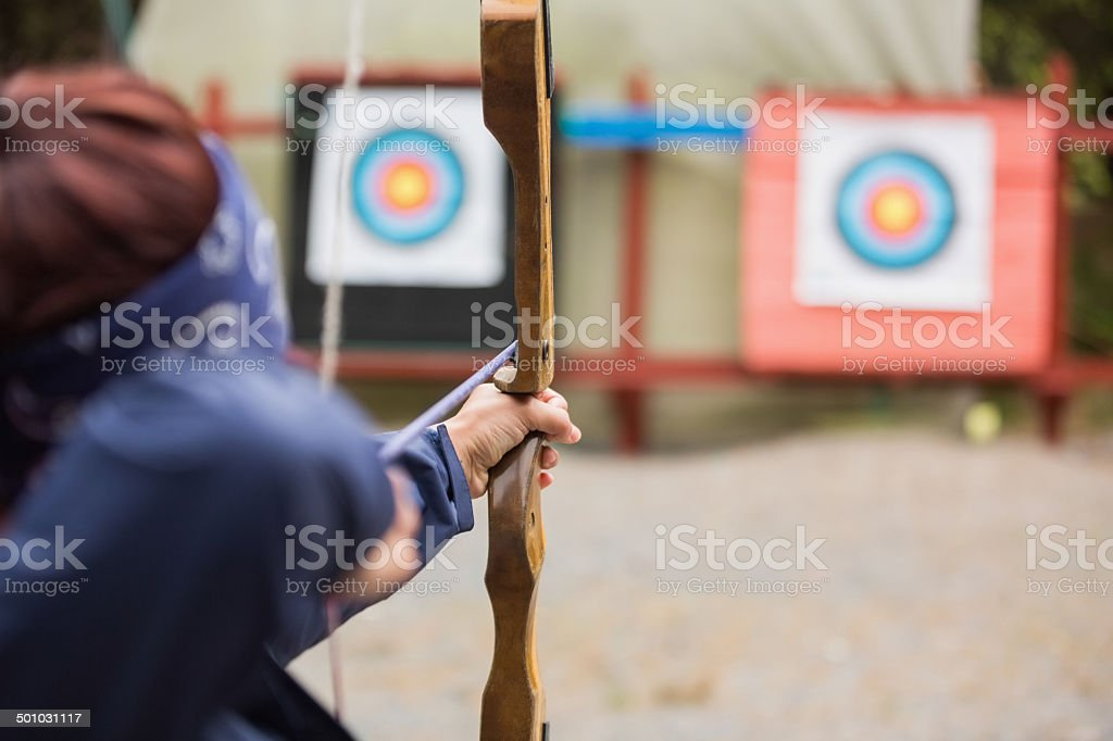 Brunette about to shoot arrow stock photo