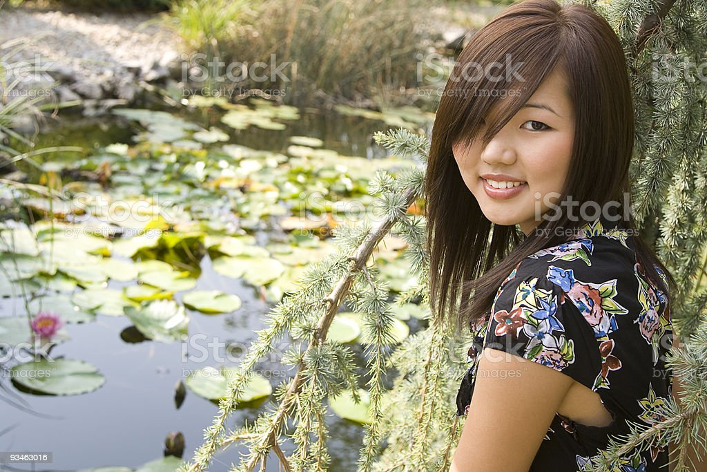 Brunette asian girl sitting at the lakeside. stock photo