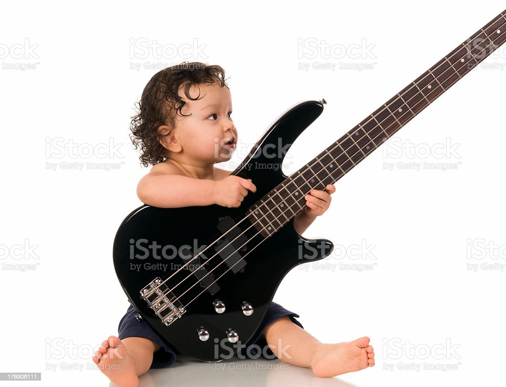 Brunette baby holding a black guitar stock photo