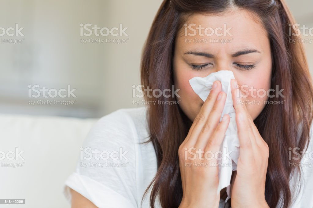 Brunette blowing nose into tissue stock photo