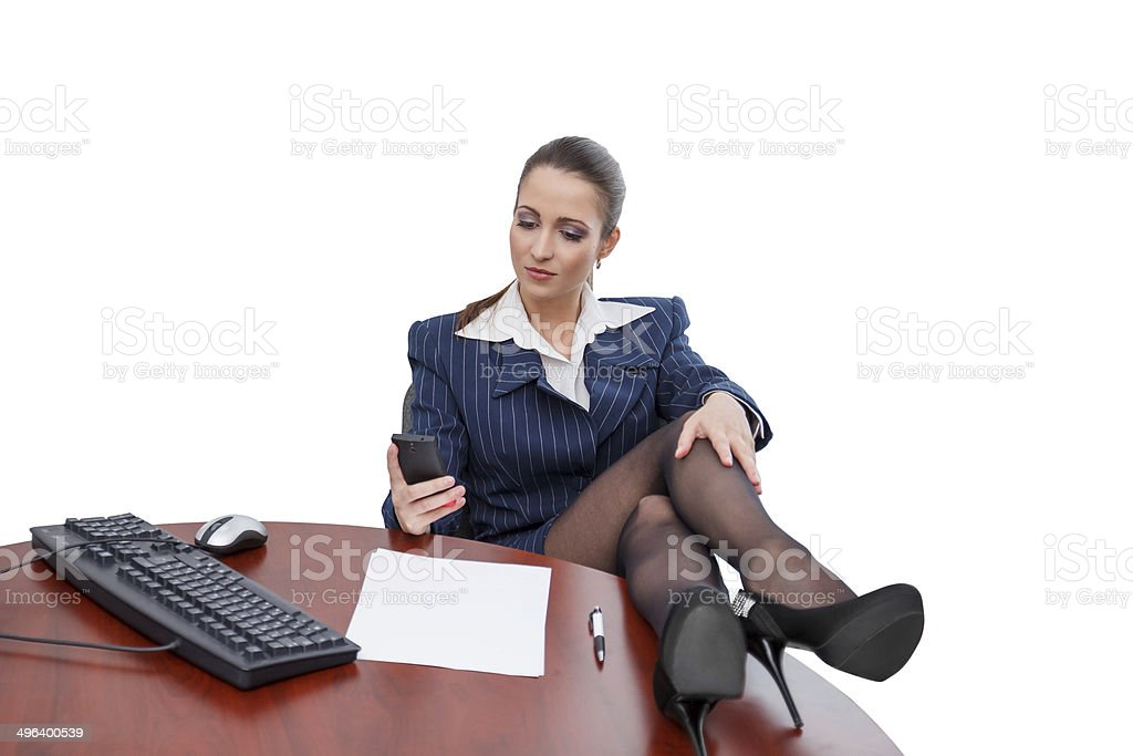 Brunette businesswoman sitting at desk with smartphone royalty-free stock photo