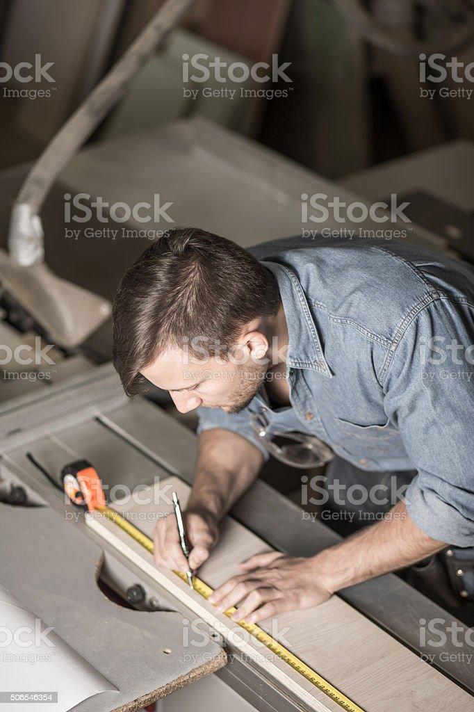 Brunette carpenter highlighting board shape stock photo