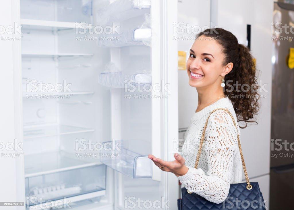 brunette choosing new refrigerator stock photo