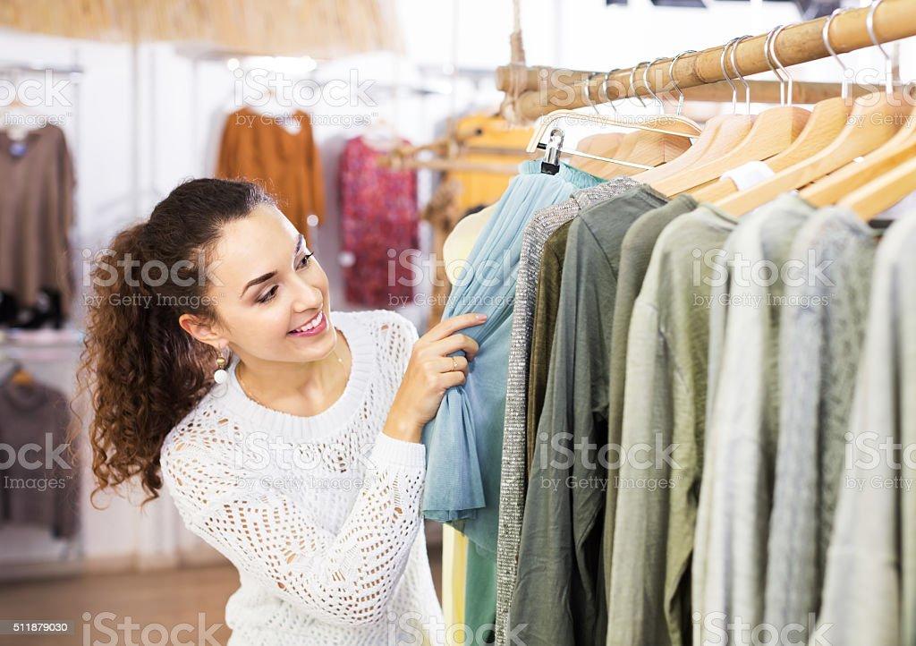 Brunette choosing skirt in shop stock photo
