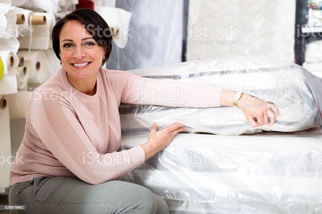 Brunette choosing sleeping mattress stock photo