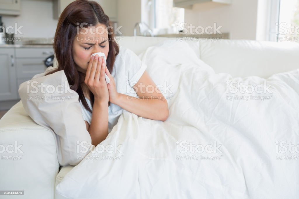 Brunette feeling ill on sofa stock photo