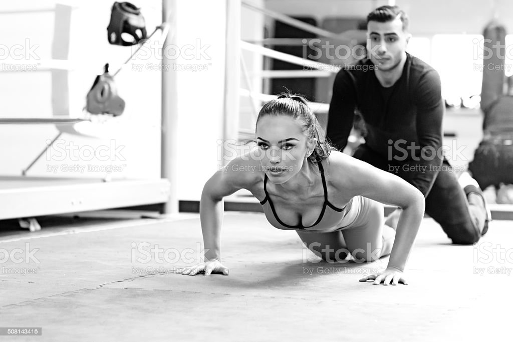 Brunette female working out at a gym with personal trainer stock photo