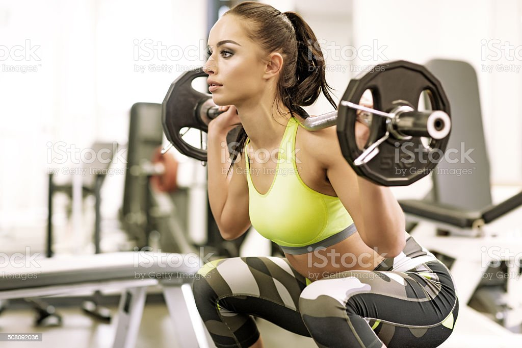 Brunette female working out with weights at a gym stock photo