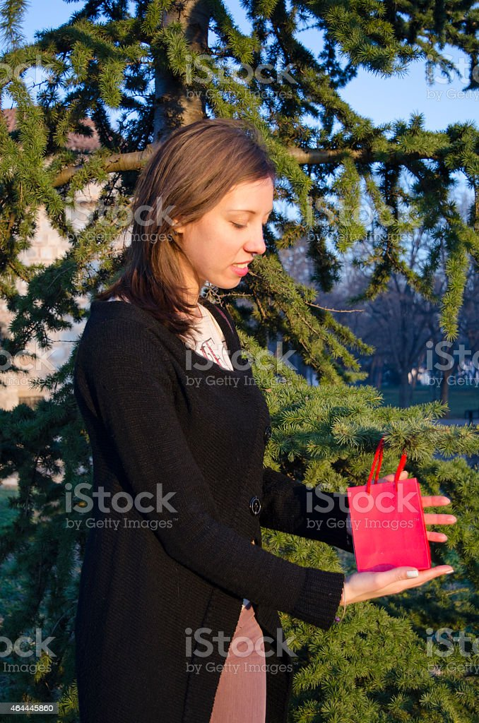 Brunette finding her Valentine's gift on a tree royalty-free stock photo