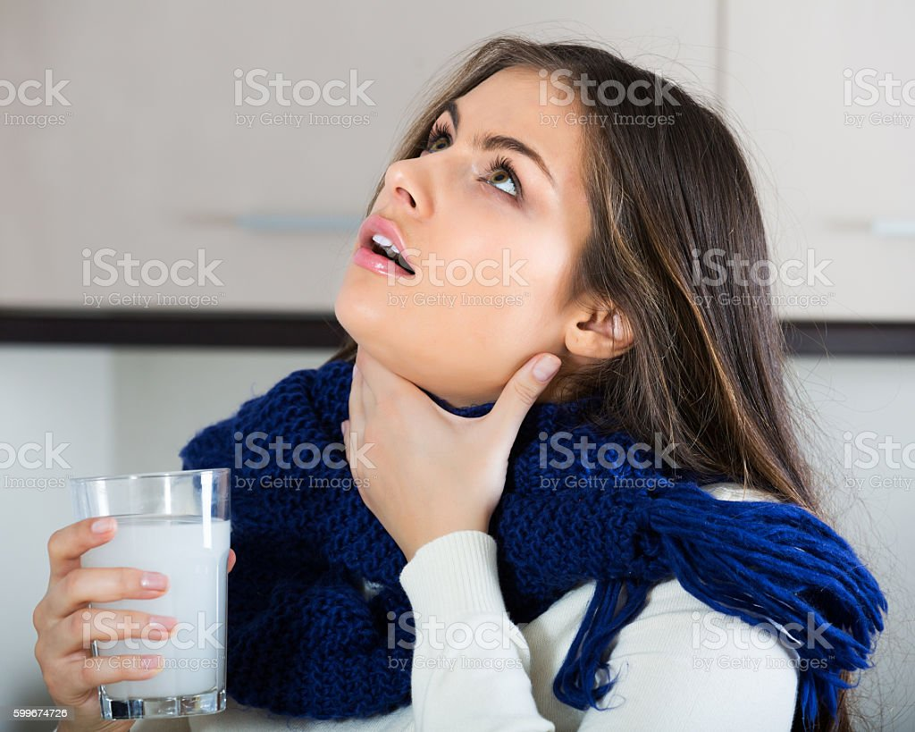 Brunette gargling throat with medicine stock photo