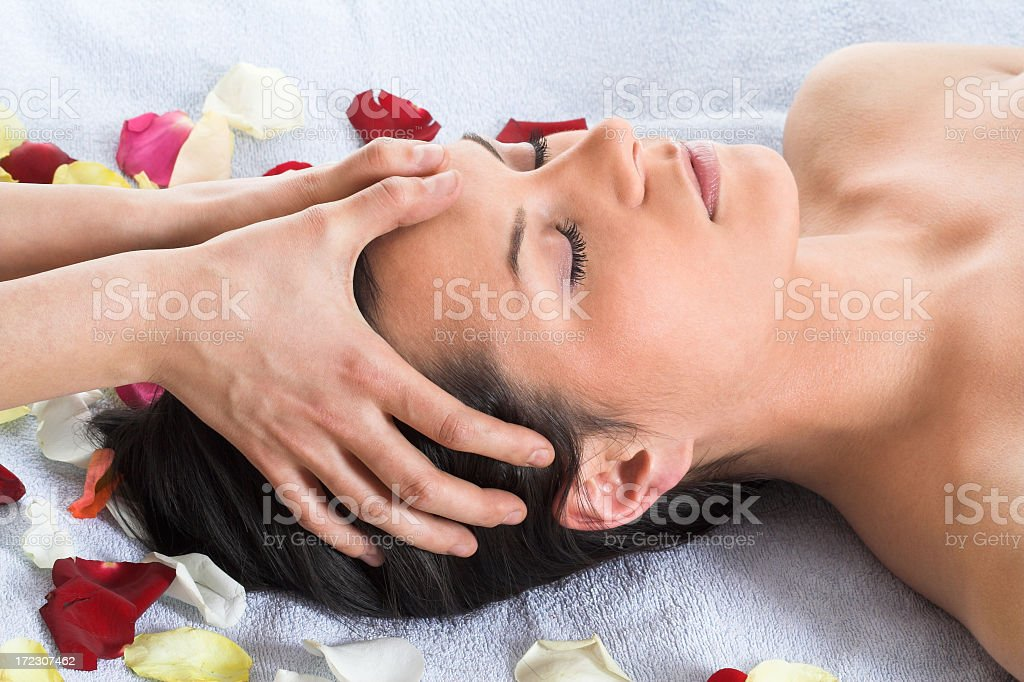 Brunette getting a head massage laying on a white towel royalty-free stock photo