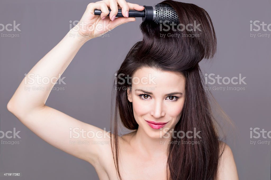 Brunette girl brushing her hair stock photo