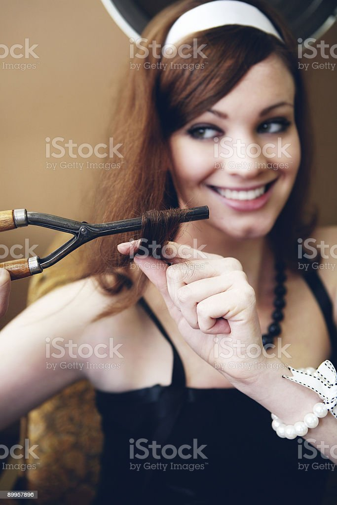 Brunette Girl Curling her Hair with Antique Iron stock photo