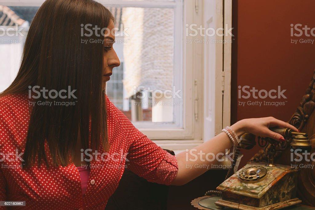 Brunette girl picking up vintage style telephone handset stock photo