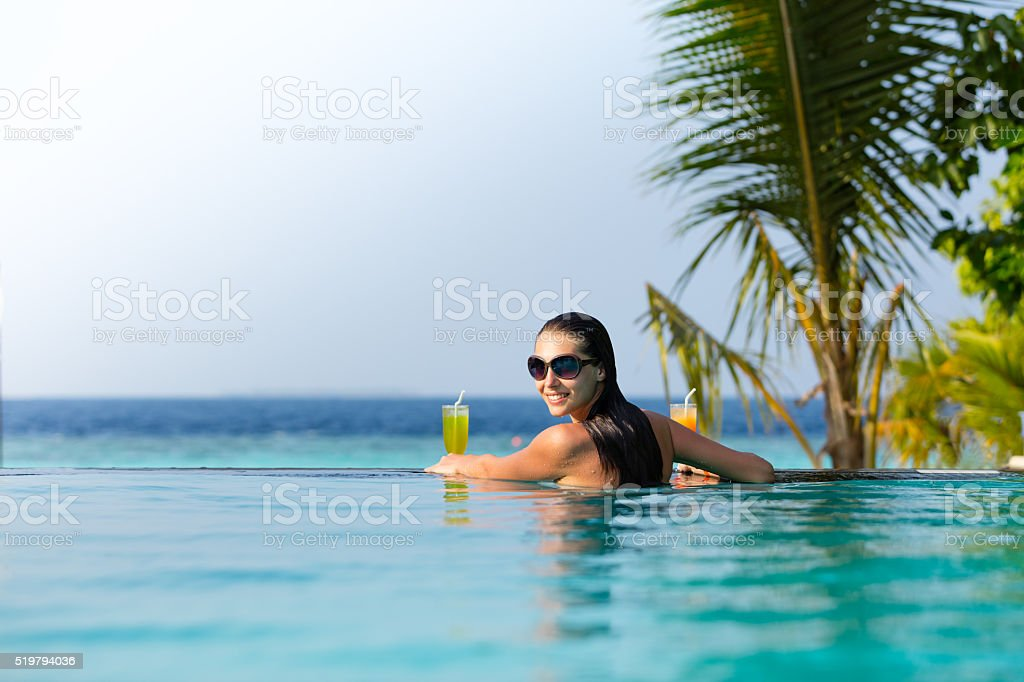 Brunette girl with cocktails in swimming pool stock photo