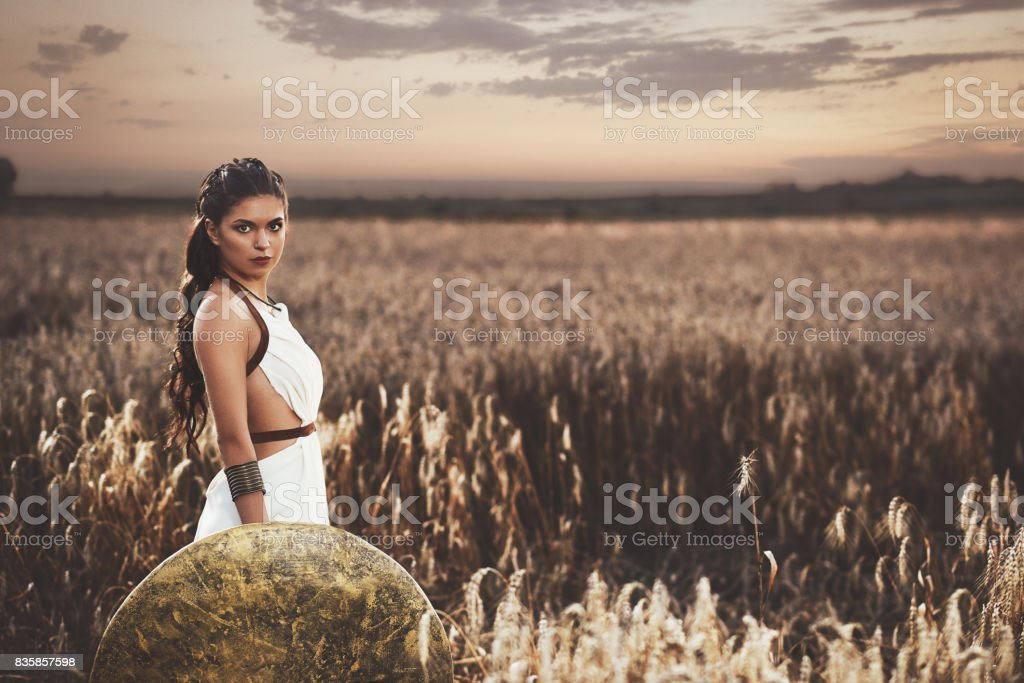 Brunette holding shield and waiting husband after war. stock photo