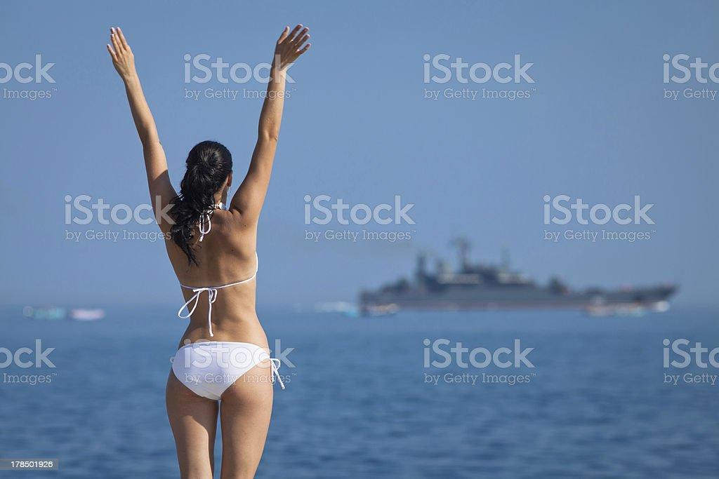 Brunette in white swimwear observes ship waving his hands royalty-free stock photo