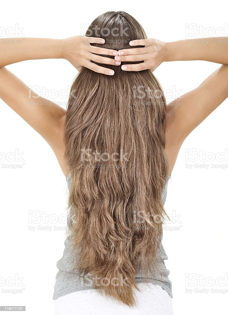 Brunette lady holding long hairs, view from back side stock photo