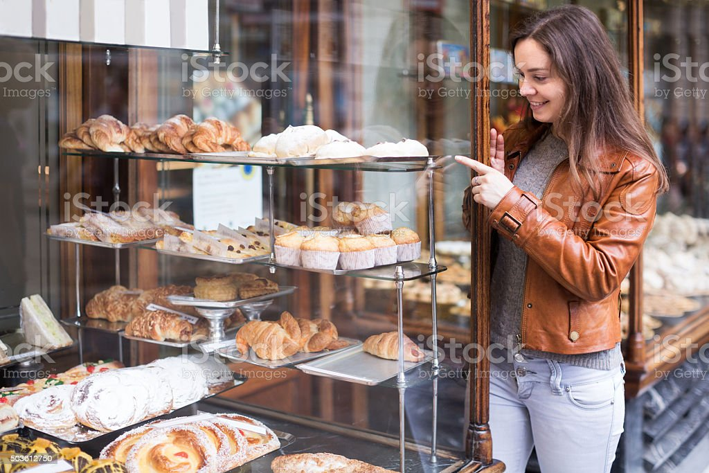 Brunette looking at fancy cakes stock photo