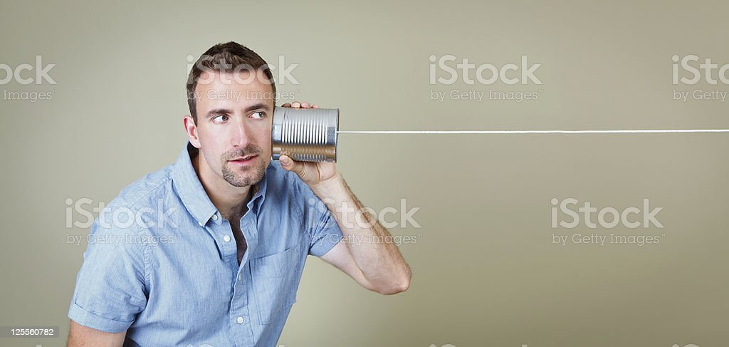 Brunette man in blue shirt listening to a tin can telephone stock photo