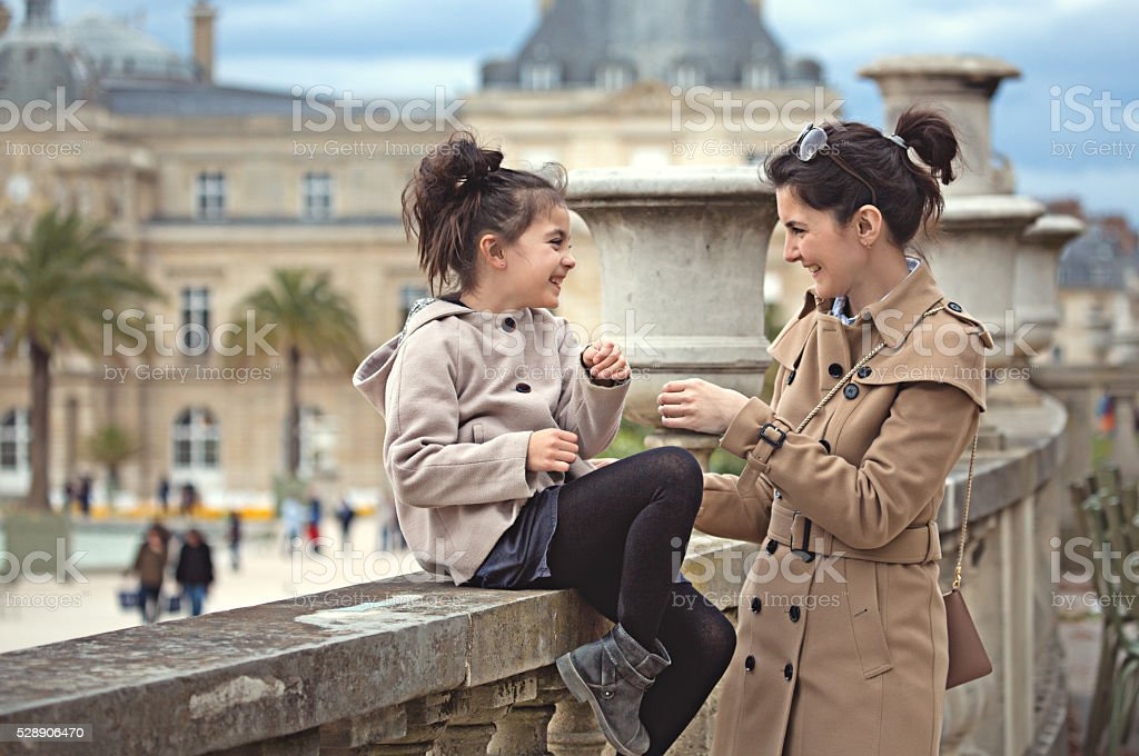 Brunette mother daughter smiling in Paris park on spring afternoon stock photo