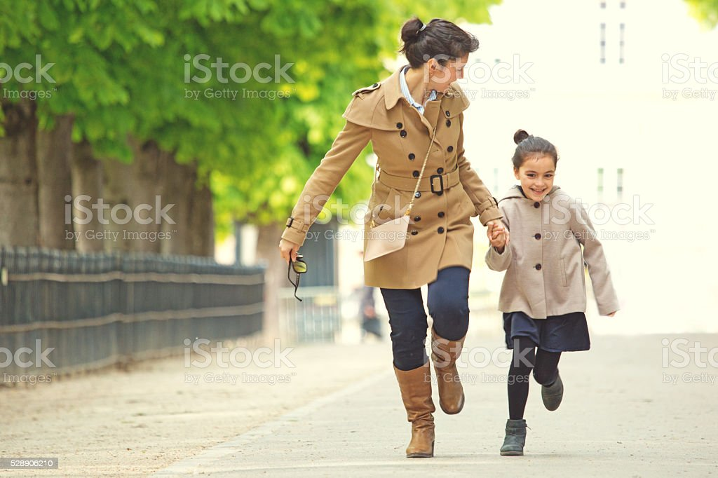 Brunette mother daughter walking in Paris park on spring afternoon stock photo