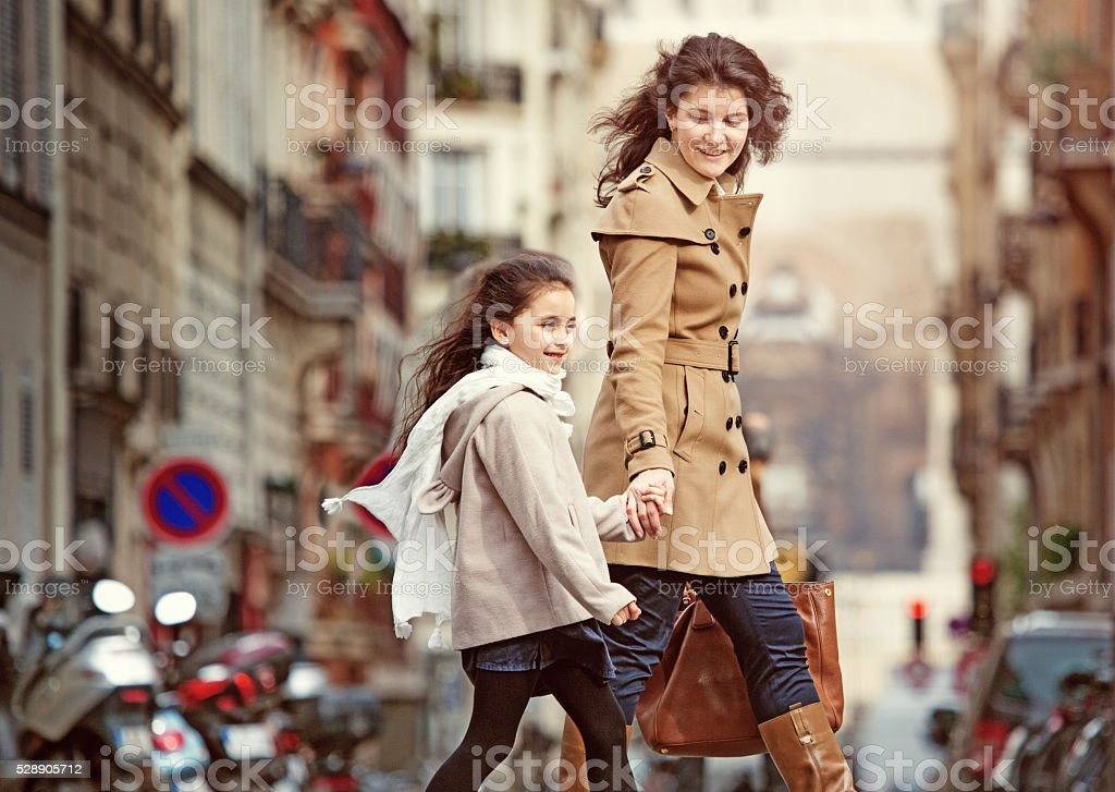 Brunette mother daughter walking in Paris streets on spring afternoon stock photo